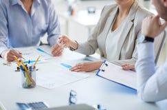 Commercieel team die grafieken bespreken op kantoor stock afbeelding