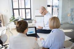 Commercieel team die grafieken bespreken op kantoor stock fotografie