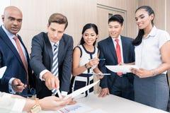 Commercieel team die grafieken en aantallen in vergadering bespreken Royalty-vrije Stock Foto