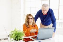 Commercieel team die in het bureau samenwerken Midden oude onderneemster en hogere zakenman die aan nieuw project werken stock foto
