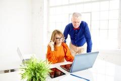 Commercieel team die in het bureau samenwerken Midden oude onderneemster en hogere zakenman die aan nieuw project werken royalty-vrije stock afbeeldingen