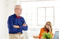 Commercieel team die in het bureau samenwerken Midden oude onderneemster en hogere zakenman die aan nieuw project werken royalty-vrije stock afbeelding
