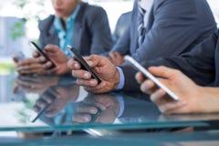 Commercieel team die hun mobiele telefoon met behulp van Stock Afbeeldingen