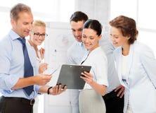 Commercieel team die iets in bureau bespreken Stock Fotografie