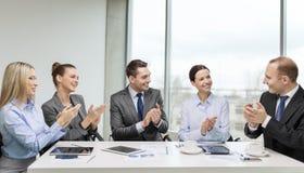 Commercieel team die met laptop handen slaan Stock Foto's