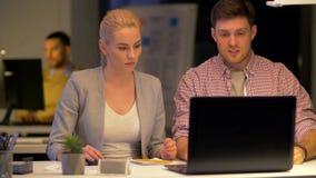 Commercieel team die met laptop op nachtkantoor werken stock video