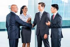 Commercieel team die overeenkomst en handdruk hebben Stock Fotografie