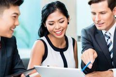 Commercieel team die project bespreken die laptop bekijken Royalty-vrije Stock Afbeeldingen