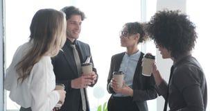 Commercieel team die terwijl het hebben van koffiepauze in bureau op elkaar inwerken stock videobeelden