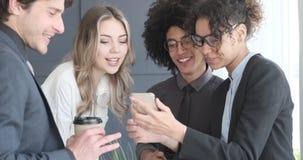 Commercieel team die terwijl het letten op de media op mobiele telefoon tevredenstellen lachen stock footage