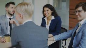 Commercieel team die terwijl het zitten in modern bureau binnen tijdens koffiepauze babbelen