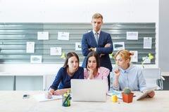 Commercieel team in een modern helder bureaubinnenland op het werk aangaande laptop stock fotografie