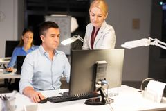 Commercieel team met computer die laat op kantoor werken stock afbeeldingen
