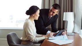 Commercieel team met documenten en tabletpc bij hotel