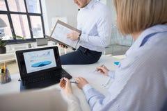 Commercieel team met grafieken op laptop op kantoor stock foto