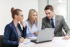 Commercieel team met laptop die bespreking hebben Stock Foto