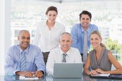 Commercieel team tijdens vergadering die bij camera glimlachen Stock Foto