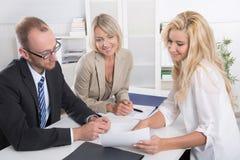 Commercieel team van de mens een vrouwenzitting rond een lijst die tog spreken Stock Fotografie