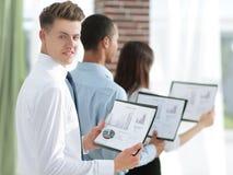 Commercieel teamfinancieel verslag die zich in een modern bureau bevinden stock fotografie