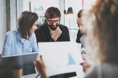 Commercieel vergaderingsconcept Medewerkersteam die met mobiele computer op modern kantoor werken Analyseer businessplannen, het  stock foto