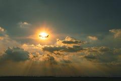 Commercieel vliegtuig die over hemel tegen mooie throu van de zonstraal vliegen stock afbeeldingen