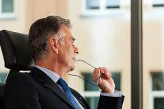 Commercio - sporgenza che contempla nel suo ufficio Immagine Stock