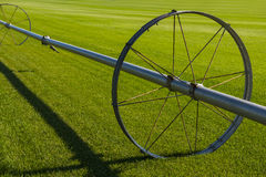 Commerical Farm Irrigation System on Wheels. Wheel line irrigation system on a green field Royalty Free Stock Images