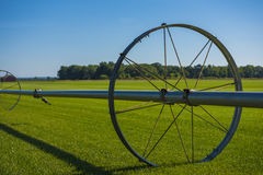Commerical Farm Irrigation System on Wheels. Wheel line irrigation system on a green field Stock Photo