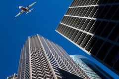 Commericial passenger plane passes over skyscrapers Royalty Free Stock Photos