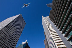 Commericial passenger plane passes over skyscrapers Royalty Free Stock Image