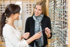 Commessa e cliente che tengono i vetri in negozio immagine stock libera da diritti