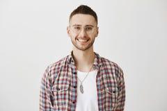 Commesso affascinante pronto ad offrire il suo aiuto Ritratto del giovane emotivo attraente con la barba nel sorridere di occhial Fotografia Stock Libera da Diritti