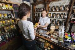 Commesso che dà prodotto al cliente femminile nel deposito del tè Immagini Stock Libere da Diritti