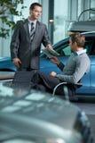Commesso dell'automobile che dà catalogo all'uomo d'affari immagine stock libera da diritti
