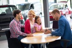 Commesso dell'automobile che dimostra nuova automobile alla famiglia immagini stock
