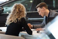 Commesso dell'automobile che parla con il cliente in sala d'esposizione immagine stock