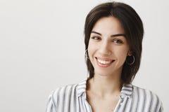 Commesso europeo attraente in orecchini e blusa alla moda che sorride largamente e gentile mentre guardando fisso alla macchina f Fotografie Stock Libere da Diritti