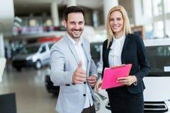 Commesso professionista che vende le automobili alla gestione commerciale al compratore Fotografie Stock Libere da Diritti