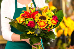 Commesso variopinto dei fiori del mazzo della tenuta del fiorista Fotografia Stock Libera da Diritti