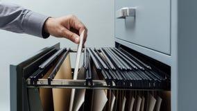 Commis de bureau recherchant des dossiers photographie stock