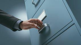 Commis de bureau recherchant des dossiers dans le meuble d'archivage photo stock