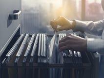 Commis de bureau recherchant des dossiers dans le meuble d'archivage photos stock