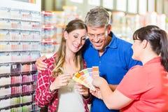 Commis de magasin d'amélioration de l'habitat conseillant des clients au sujet de couleur photos stock