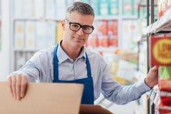 Commis de supermarché au travail image stock