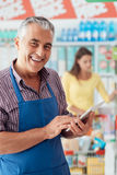 Commis de supermarché utilisant un comprimé images stock