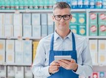 Commis de supermarché utilisant un comprimé photographie stock libre de droits