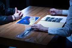 Commissioner showing murder weapon. Commissioner showing photos and murder weapon to suspect royalty free stock photos