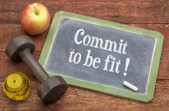 Commit to be fit - motivation concept on blackboard. Commit to be fit motivation concept - slate blackboard sign against weathered red painted barn wood with a royalty free stock image