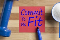 Commit To Be Fit written on note. With sport supplement and dumbbell on wooden desk. Top view Royalty Free Stock Photos