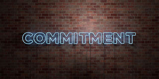 COMMITMENT - fluorescent Neon tube Sign on brickwork - Front view - 3D rendered royalty free stock picture Stock Photo